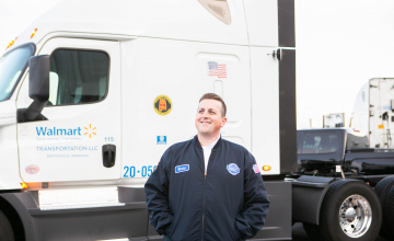 walmart employee smiling in front of truck