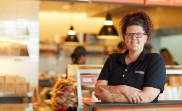 Chipotle employee smiling in restaurant thanks to education benefits